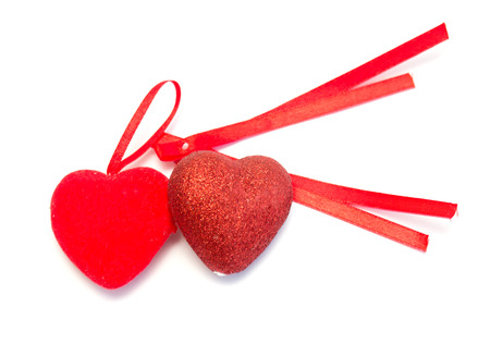 two red hearts with red ribbon on white background photo