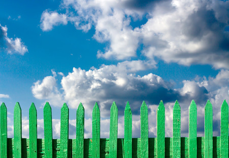 green wooden fence on a blue sky background photo