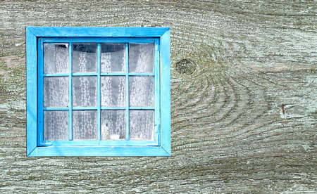 Old window of a wooden house wall