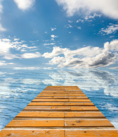 berth: wooden pier on sunny day with white clouds and sun