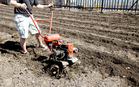 motor hoe: Small rotary cultivator, man  working in garden Stock Photo