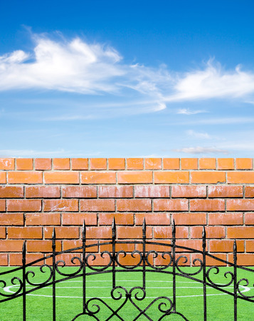 Old brick wall, metal fence and green grass on a sky background photo