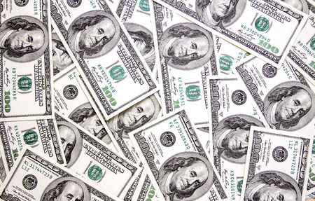 Benjamin Franklin 100 dollar bills arranged randomly with the portrait facing uppermost in a closeup conceptual financial and monetary background