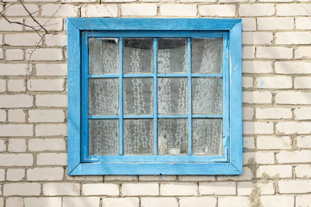 hollow walls: blue frame window in a brick wall