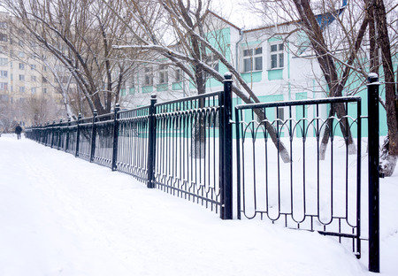 frost bound: Winter metal fence in the snow