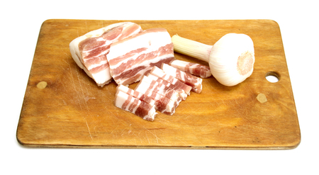 salo: White pork lard called salo with garlic and pepper on wooden kitchen table