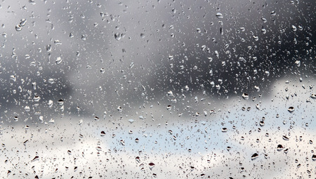 window pane: Raindrops on a window pane on the background of a stormy sky.