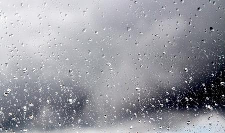 gotas de agua: Gotas de agua en un cristal de la ventana en el fondo de un cielo tormentoso.