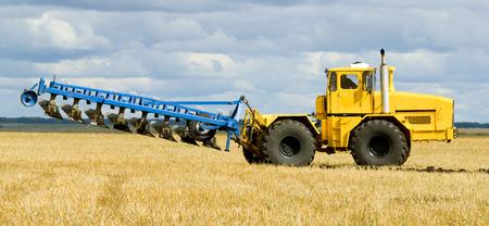 arando: Amarillo tractor para trabajo pesado listo para arar, paisaje de oto�o Foto de archivo
