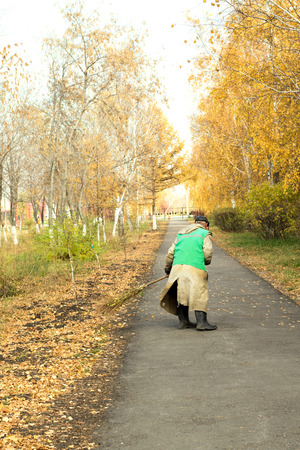 sweeps: janitor sweeps the street, autumn