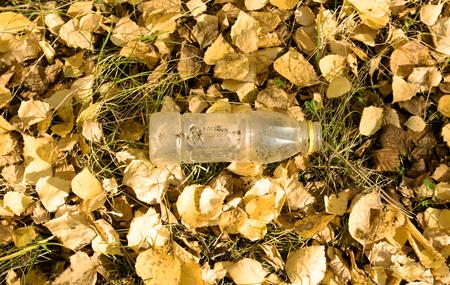 needless: trash, plastic ware on yellow leaves