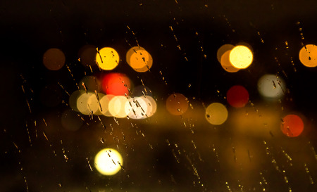 defocussed: Abstract night city light and bokeh through car windscreen covered in rain, defocussed background Stock Photo