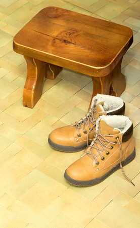 muddy clothes: yellow shoes on the floor with a stool