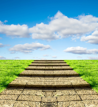 upward climb: stone steps on the grass in the sky clouds