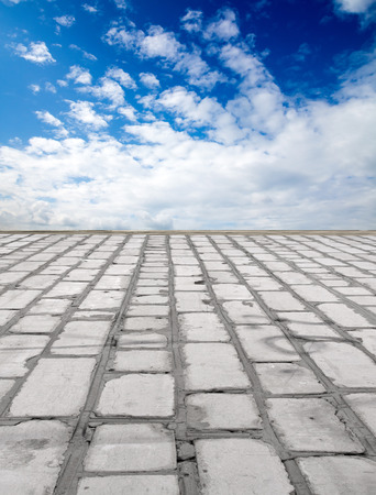 brick road: old brick road on the blue sky background Stock Photo