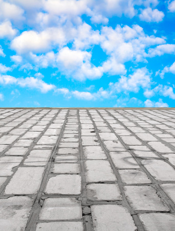 stone road: old brick road on the blue sky background Stock Photo