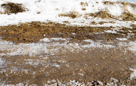 inclement weather: dirt on a snowy road Stock Photo