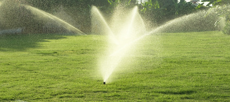 sprinkle system: Irrigation System Watering the green grass, blurred background