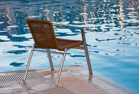 pool tables: wicker chair beside a pool.