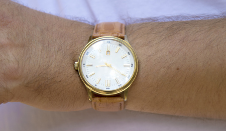 mans watch: Gold watch with white face on a mans hand