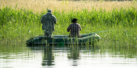 Fishermen with boats catching fish in the reeds, summer
