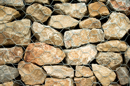 gabion mesh: Stone background with closed metal mesh Stock Photo