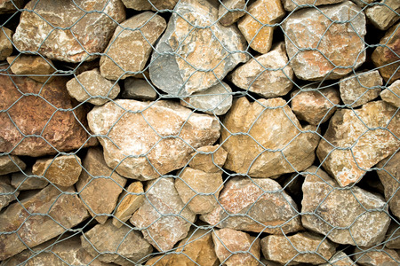 Stone background with closed metal mesh Stock Photo