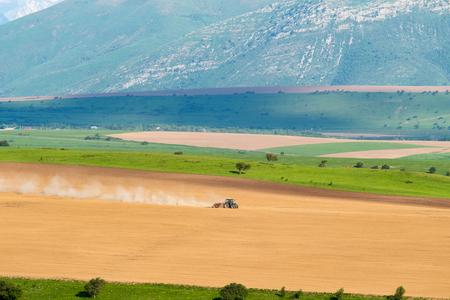 arando: Tractor ara en el campo, paisaje de montaña Foto de archivo
