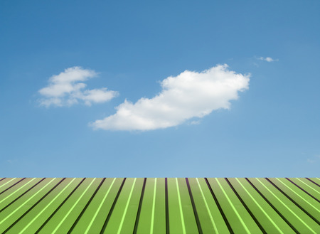 Green flooring against the sky with clouds