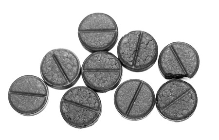 Activated charcoal pills on white background