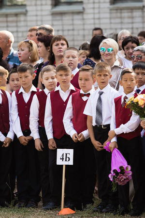 first year student: Petropavlovsk, Kazakhstan - September 2, 2017: School line is in schoolyard with pupils and teachers. Children go back to school. The Knowledge Day in Kazakhstan first day of school.