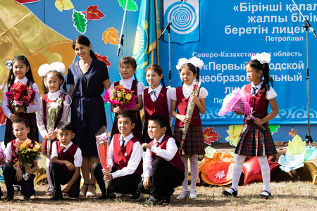 Petropavlovsk, Kazakhstan - September 2, 2017: School line is in schoolyard with pupils and teachers. Children go back to school. The Knowledge Day in Kazakhstan first day of school.