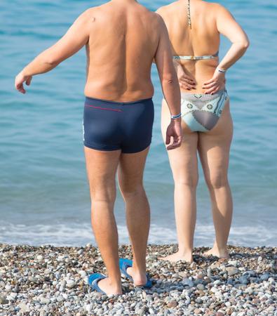 man en vrouw op het strand in zwembroek, achteraanzicht Stockfoto