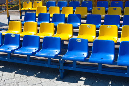 plastic seat blue yellow in the stadium Stock Photo