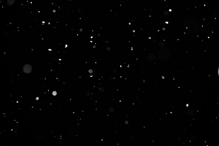 Snowstorm texture. Bokeh lights on black background, shot of flying snowflakes in the air Stock Photo