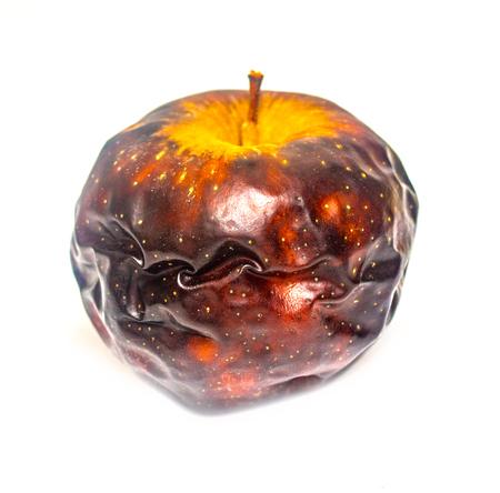old dark dried apple on a white background