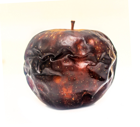 old dark dried apple on a white background