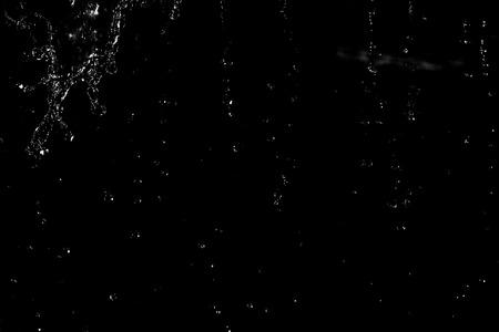 Water splash in dark with a drops of water flying, defocused bokeh.