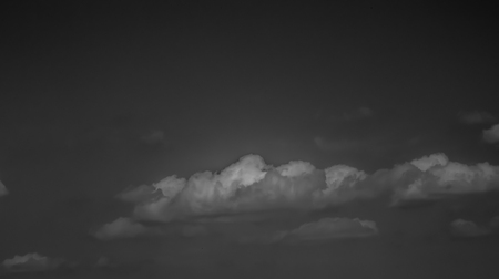 White clouds on a dark sky, monochrome.
