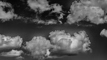 Witte wolken op een donkere hemel, zwart-wit.