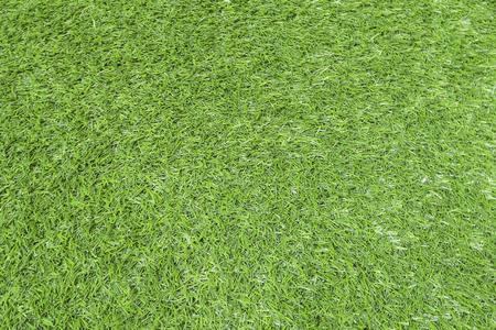 Texture of green grass, field with artificial turf for football, background.