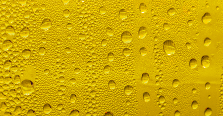 Drops of water on the glass, yellow background beer, misted background.