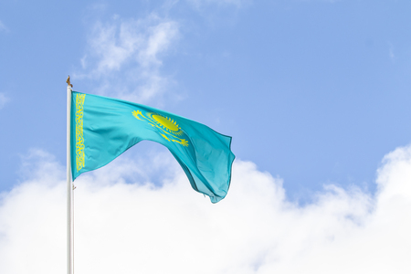Flag of the Republic of Kazakhstan against the blue sky, wind.