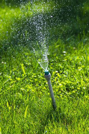 Irrigation System Watering the green grass with bokeh background. Stock Photo