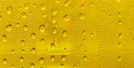 Drops of water on the glass, yellow background beer, misted background. Stock Photo