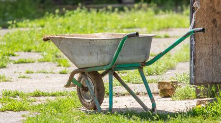 Wheelbarrow. ld yellow Trolley for construction. Using feathers, stones, sand, cement and others. Stok Fotoğraf