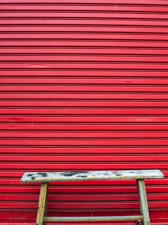 Old chair in front of red door photo
