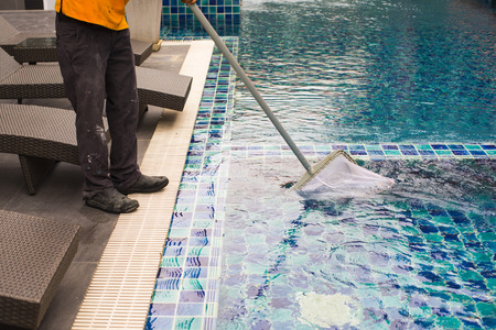 Man cleaning the swimming pool.