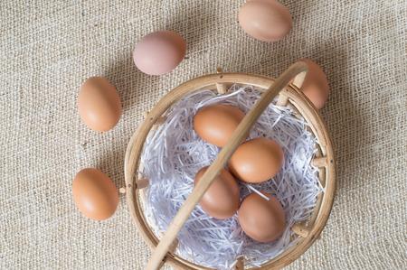 sacco juta: Eggs in bamboo basket on jute sack