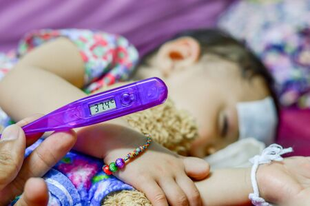 Sick baby and lying measuring electric thermometer